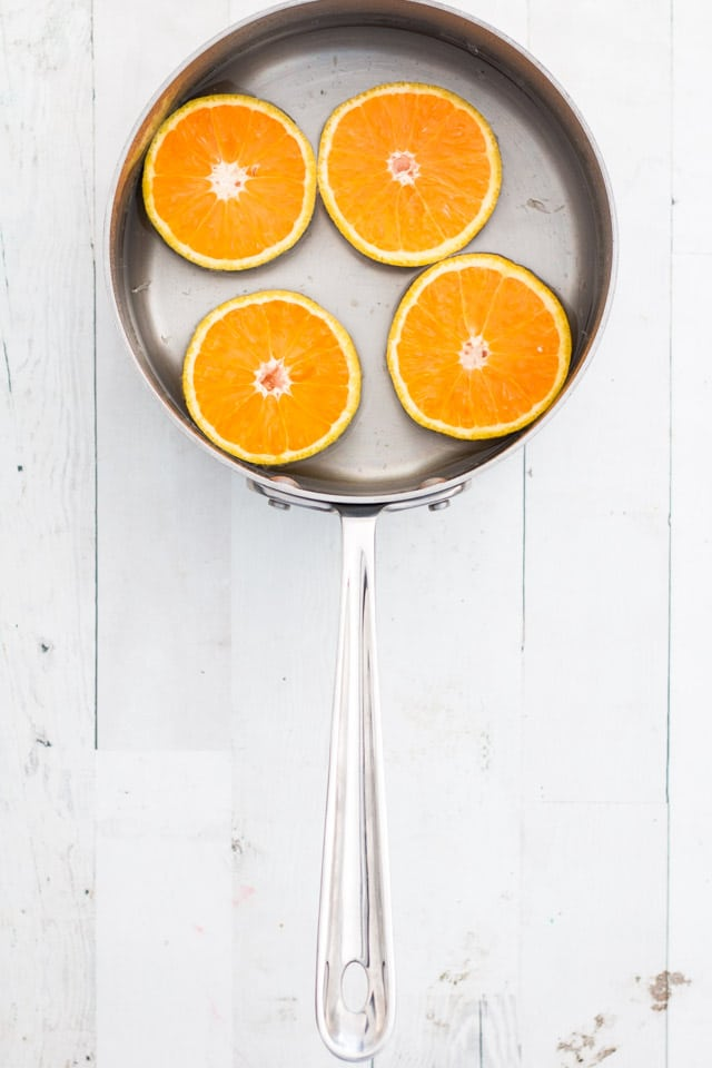 overhead shot of 4 orange halves covered in water in a small stainless steel saucepan