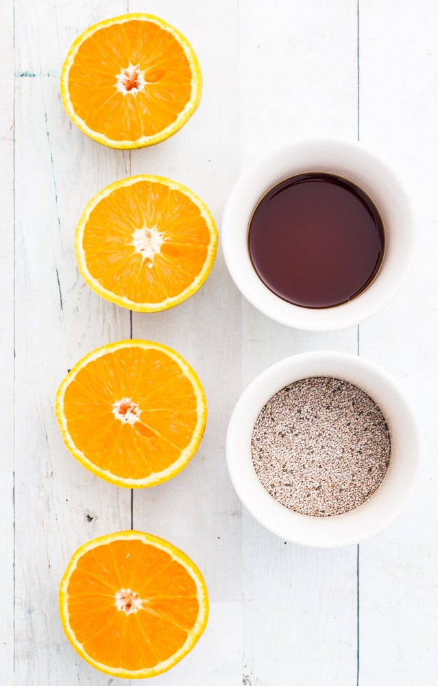 Overhead shot of halved oranges, maple syrup and chia seeds