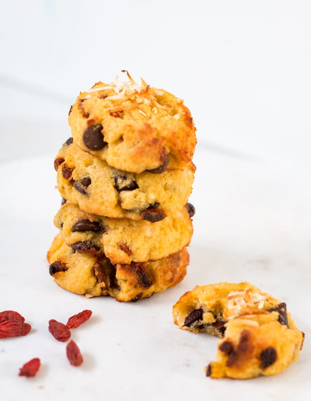 a stack of 4 cookies against a white background with goji berries sprinkled around the stack