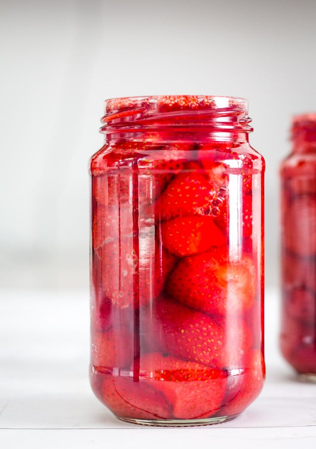 Tall glass jar filled to the brim with baked strawberries and syrup