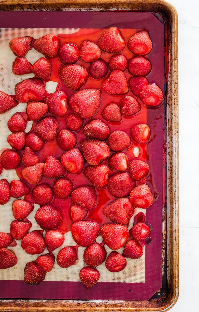 Baked strawberries on a silicone baking sheet oozing strawberry juice