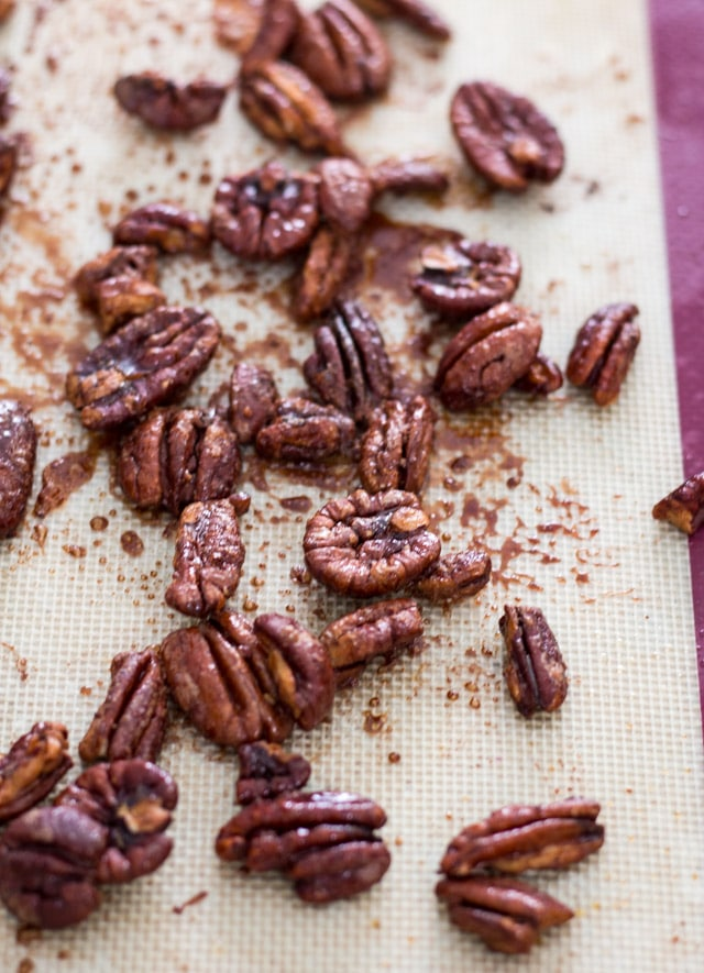 overhead shot of roasted pecans on a silicone baking sheet