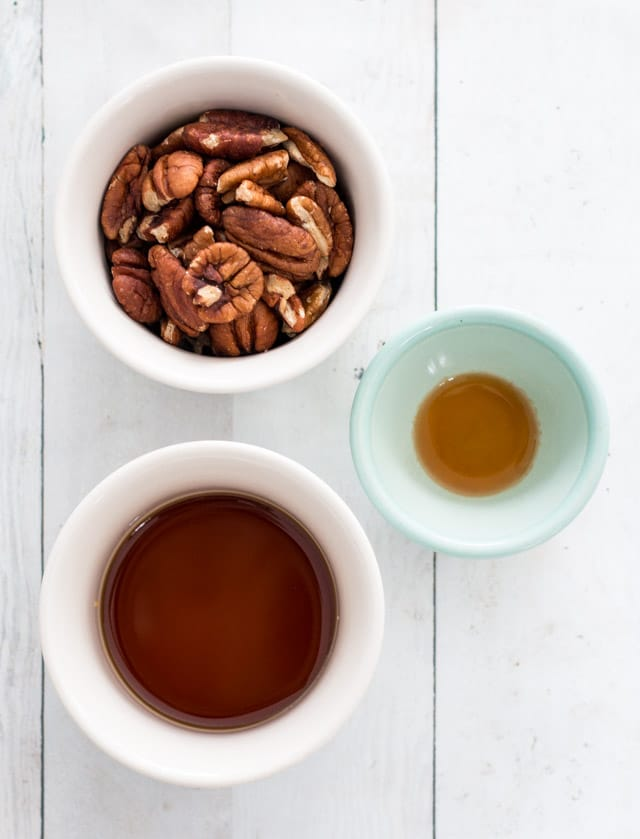Overhead ingredient shot of pecans, maple syrup and vanilla, required for maple glazed pecans