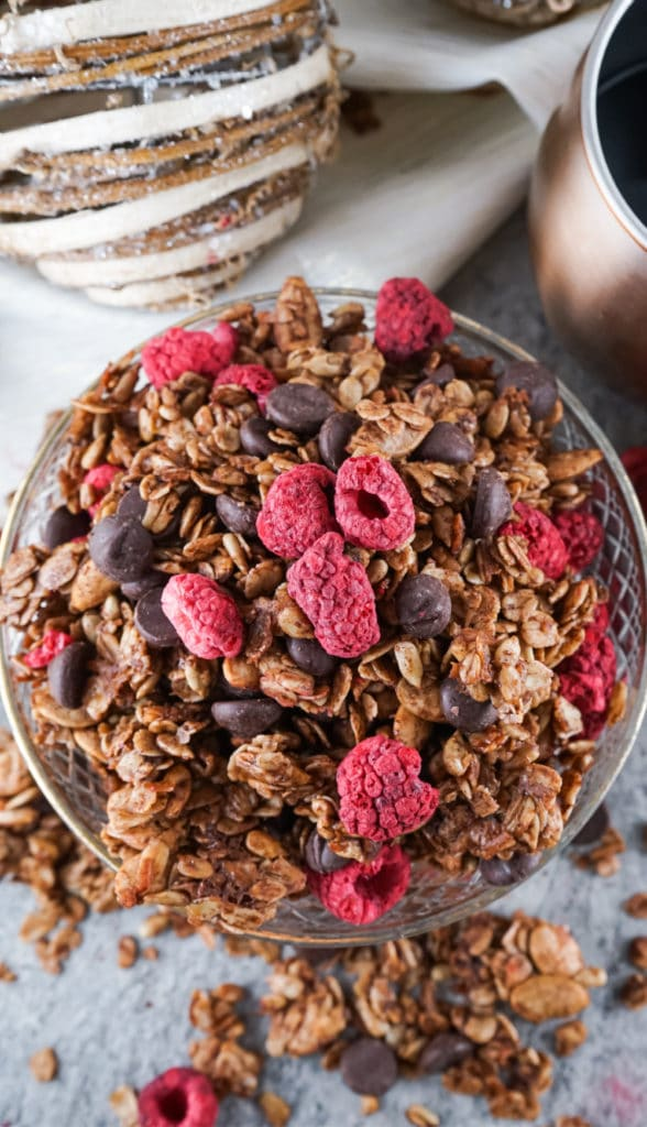 Overhead shot of chocolate granola with lots of raspberries on top and a christmas bauble in the background