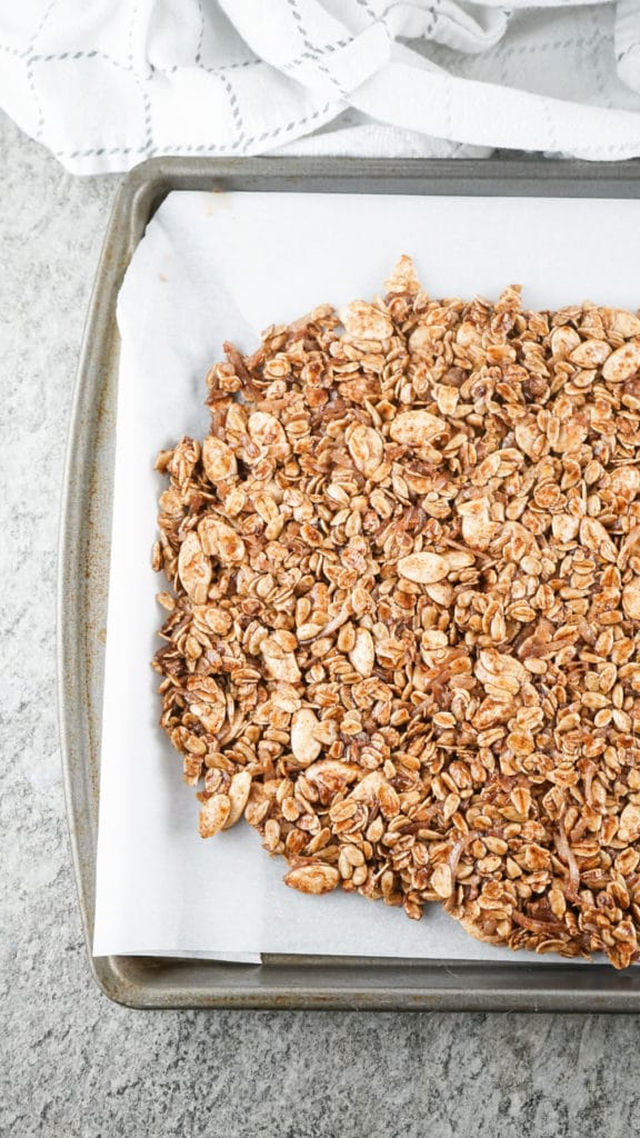 uncooked granola on a baking tray lined with parchment paper