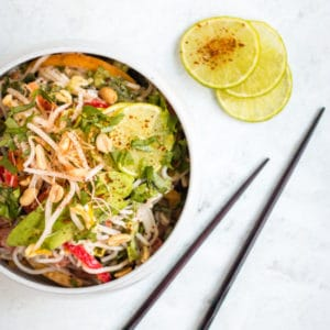 Cold peanut noodle salad served in a large white bowl against a grey background with wooden chopsticks and chilli covered lime in the background