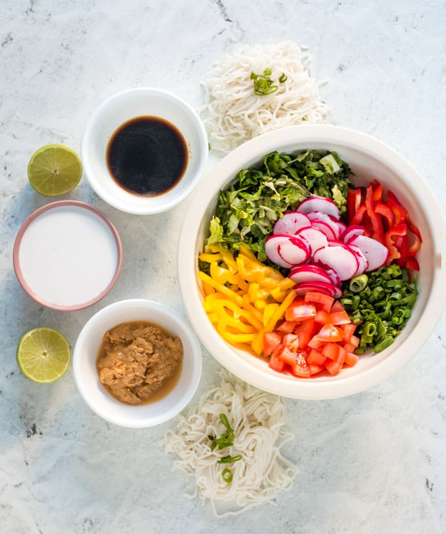 Ingredients for peanut butter noodles displayed in small bowls against a grey background