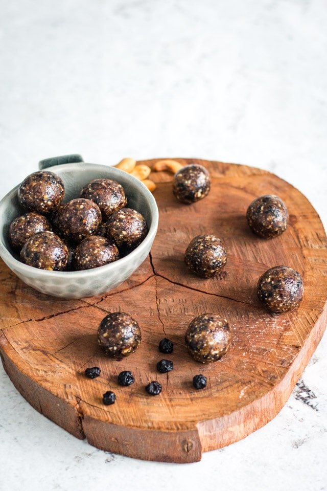 Blueberry bliss balls served up on a wooden board with a small grey bowl containing a pile of the bliss balls