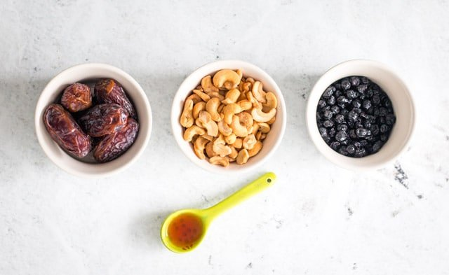 Overhead ingredient shot for dried blueberry bliss balls with small bowls containing dates, cashews, dried blueberries and vanilla