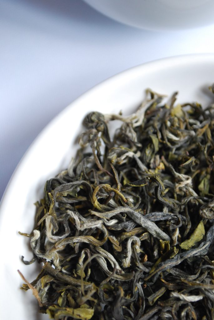 loose leaf green tea leaves in a white bowl