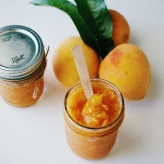 3 Ingredient Peach Butter in mason jars with 3 fresh peaches in the background