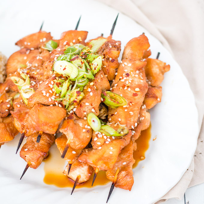 pile of teriyaki chicken skewers on a white plate topped with chopped spring onions