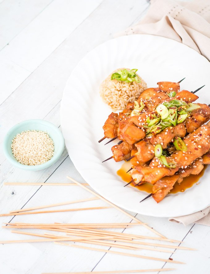 Teriyaki chicken skewers piled onto a white plate with a green bowl of sesame seeds on the side