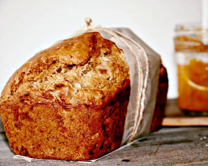 Front view of banana and peach butter bread with a jar of peach butter in the back