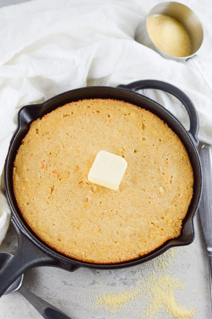 homemade cornbread in a black cast iron skillet with a cube of butter on top