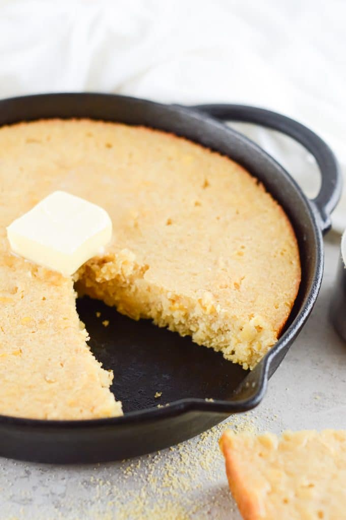 Homemade honey butter cornbread in a cast iron skillet with a dollop of butter on top