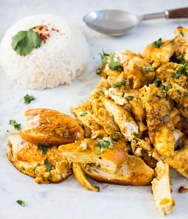 A pile of sliced baked chicken with a turmeric sauce and a mound of rice in the background