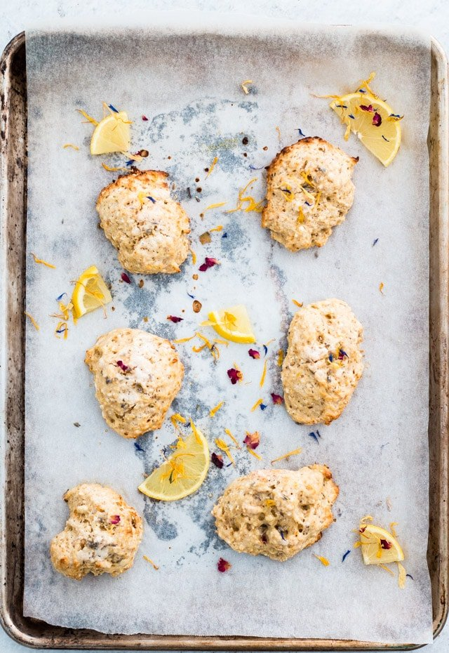 Overhead shot of 6 lemon and lavender scones on a baking tray and sprinkled with edible flowers and small lemon wedges
