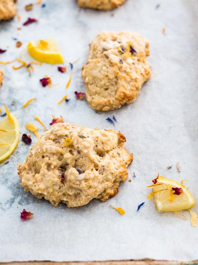 vegan lemon scone on a baking sheet surrounded by sprinkles of edible flowers