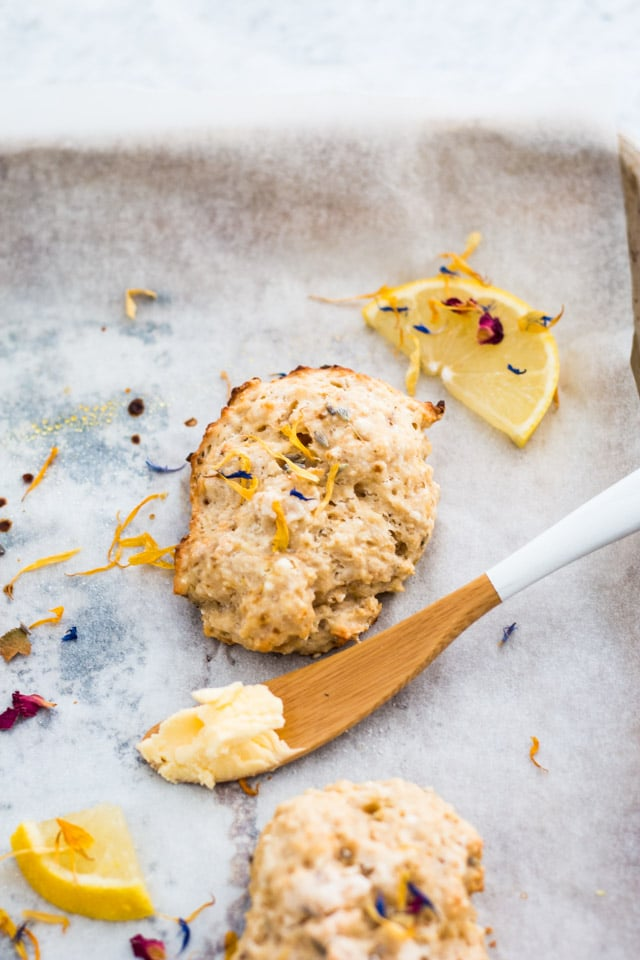 Overhead shot of a lemon and lavender scone on a baking tray and sprinkled with edible flowers and small lemon wedges