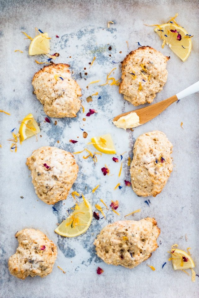 Overhead shot of 6 lemon and lavender scones on a baking tray and sprinkled with edible flowers and small lemon wedges with a butter knife on the side