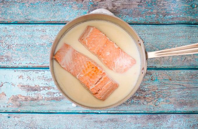 poached salmon in a saucepan of warm milk
