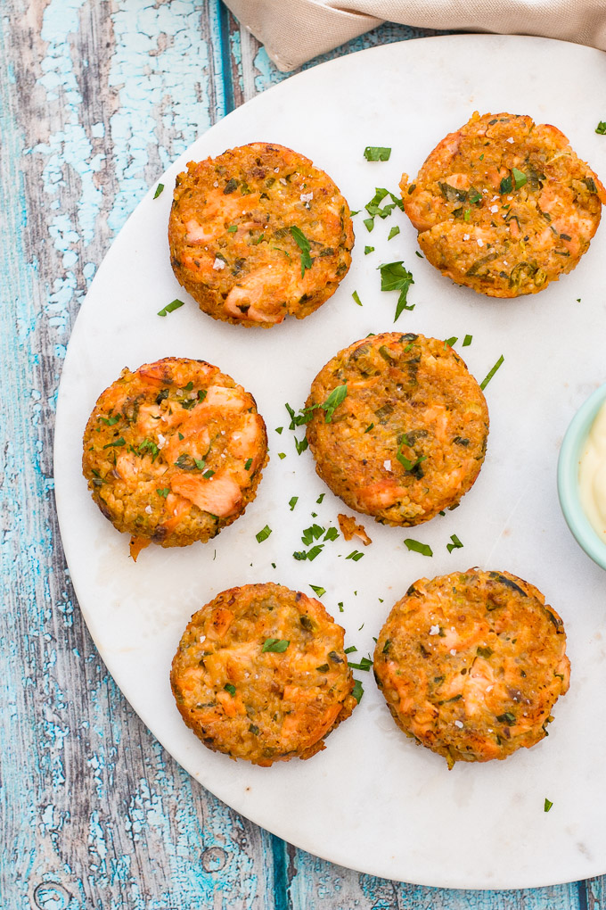 Quinoa and salmon burgers laid out on a white platter with a sprinkling of fresh parsley