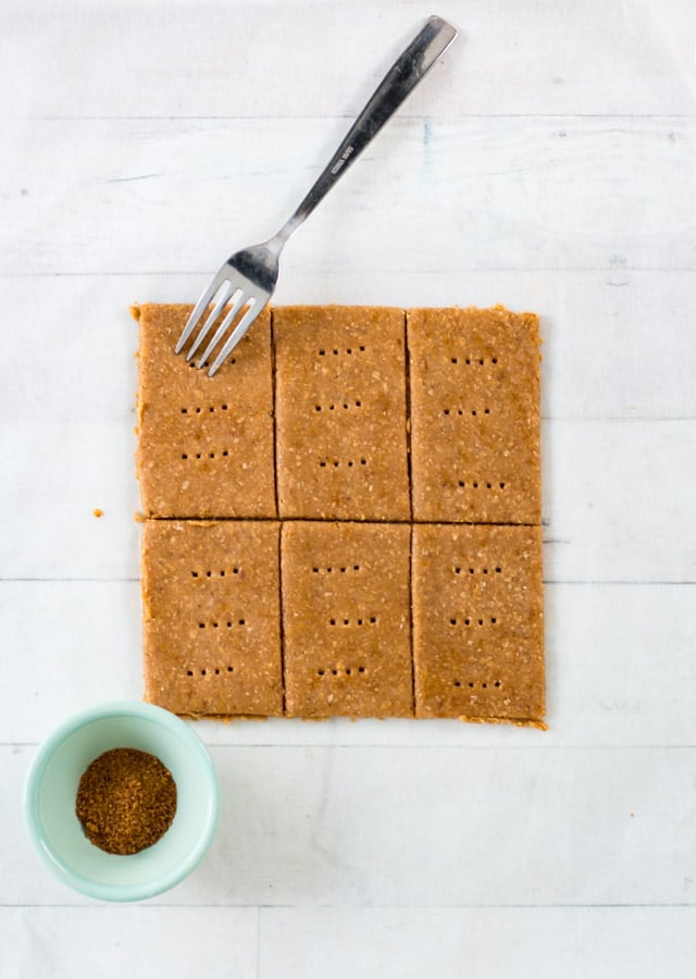 6 uncooked graham crackers on a sheet of parchment paper and a fork poking holes on top