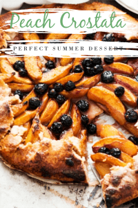 Blueberry and peach crostata with a slice being removed by a cake slice