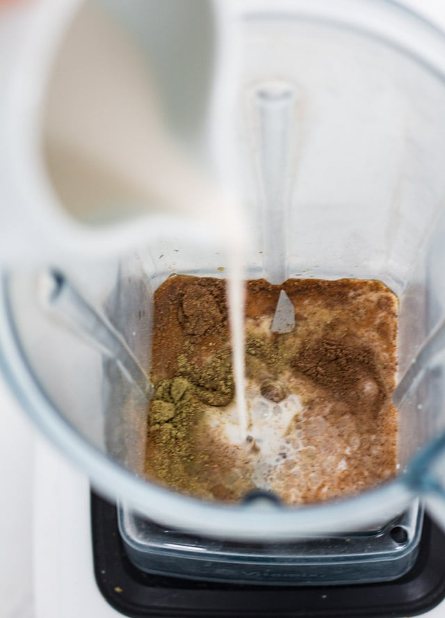 Blender jug being filled with spices and milk for making a green tea latte