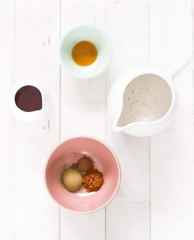 A collection of ingredients required for green tea chai latte displayed in small bowls
