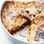 A large cake tin filled with baked oatmeal and missing a slice