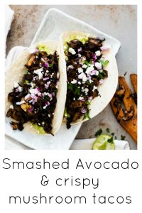 Mushroom and smashed avocado tacos on a steal background with a wooden spoon and limes surrounding