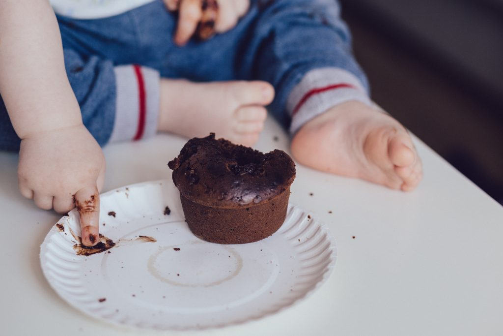 child eating chocolate muffin on bench