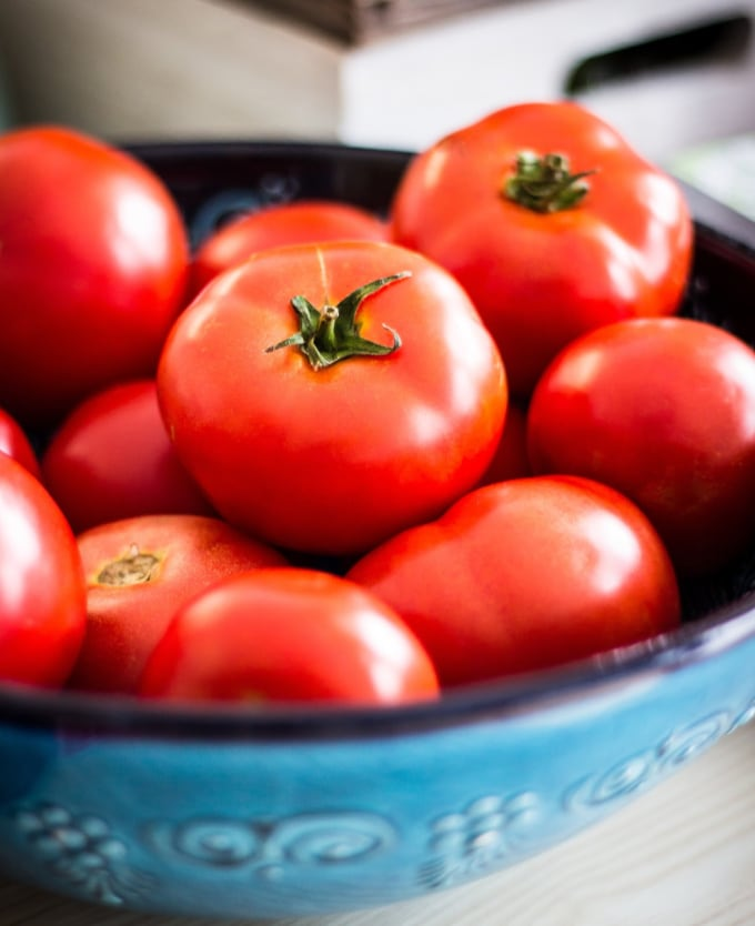 A bowl of fresh tomatoes for Eating plant based on a budget