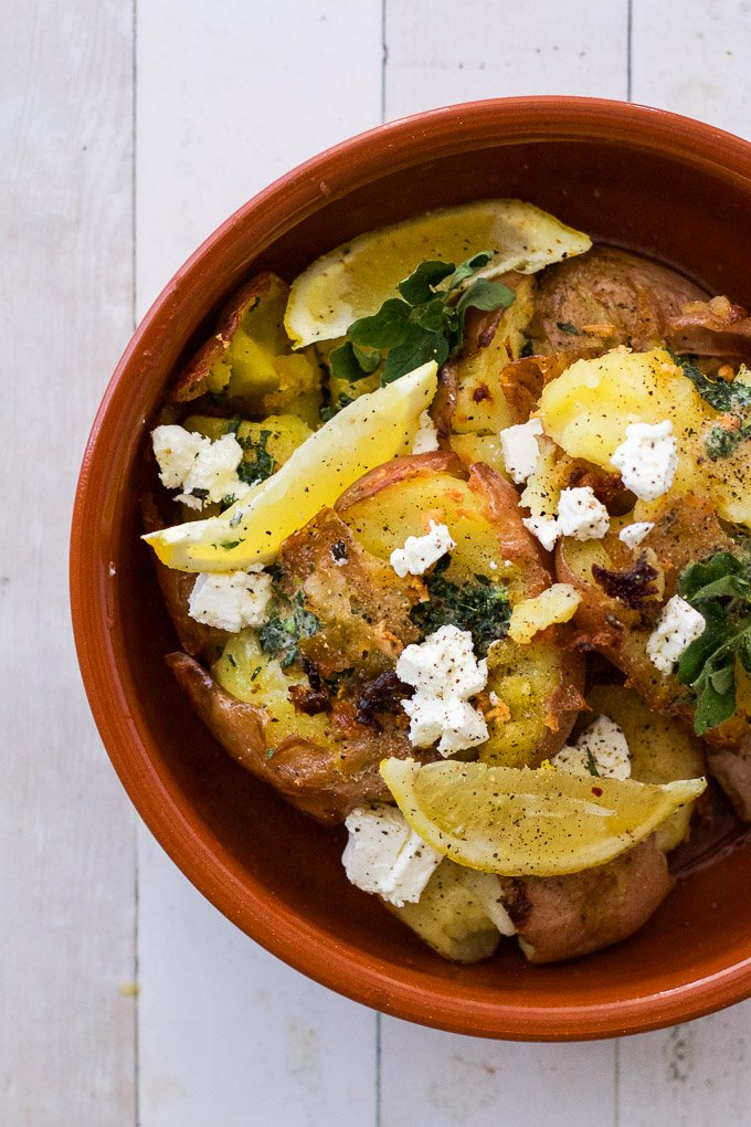 lemon garlic potatoes in a terracotta bowl with lemon wedges and feta on top