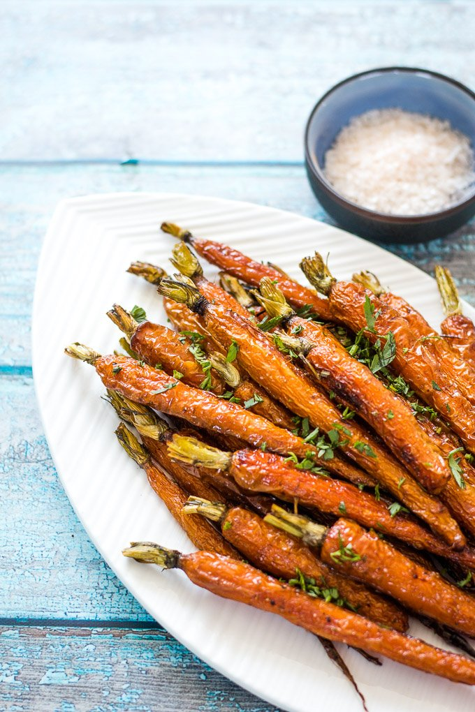 Roasted Dutch Carrots on a white platter with a side of himalayan pink salt