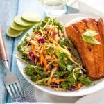 teriyaki salmon on a white plate with slaw