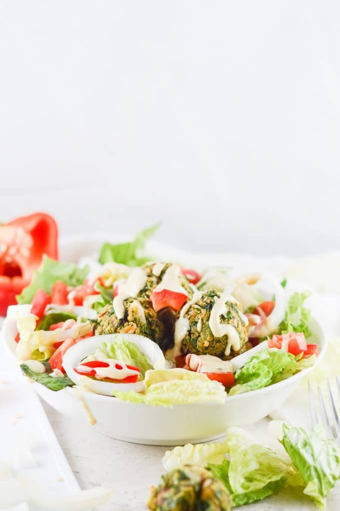 Homemade falafel salad in white bowl against a white background