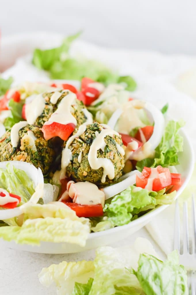 Falafel bowl with salad against a white background