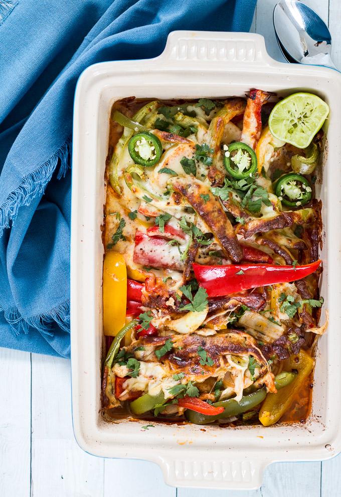 healthy chicken fajita casserole in a blue le creuset casserole dish