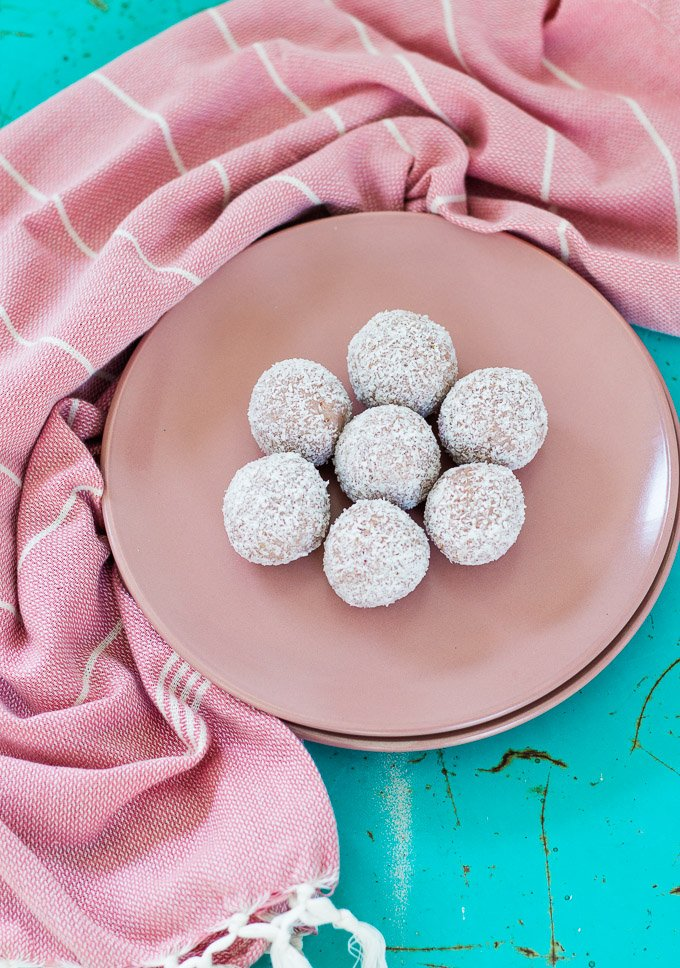 vegan bliss balls on a pink plate with a teal background