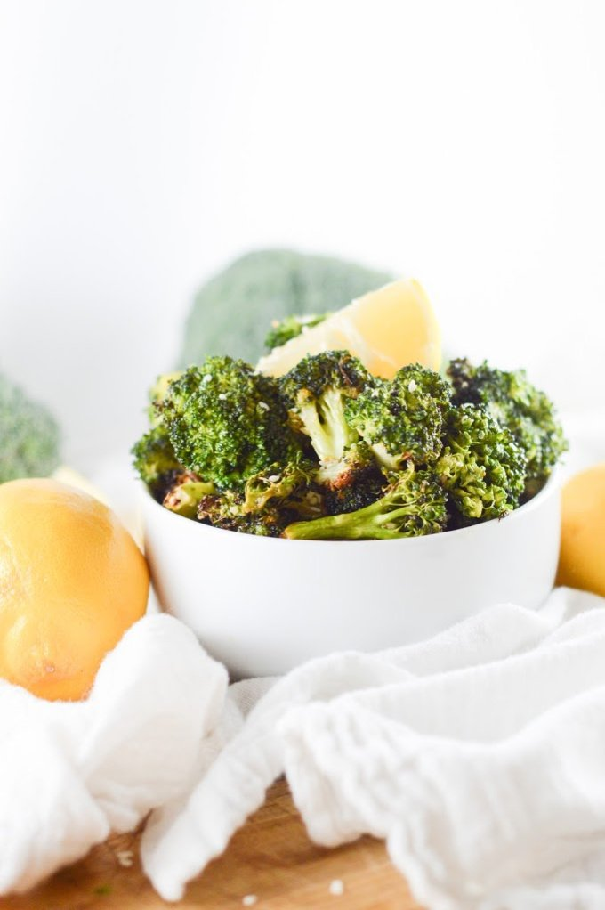 Air fryer broccoli in a white bowl with fresh lemon wedges on top