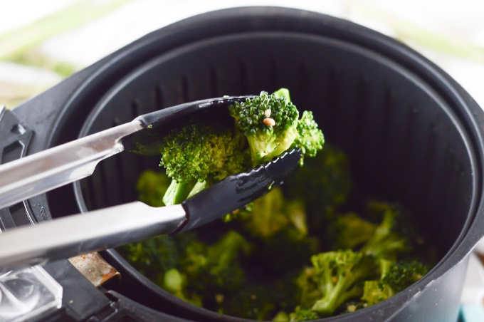 Lemon and garlic broccoli being removed from the air fryer