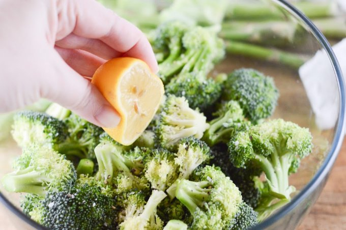 Broccoli florets in a bowl and lemon being squeezed over