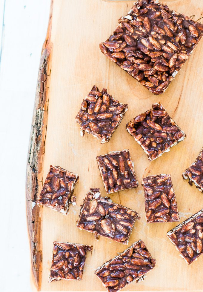 peanut butter and chocolate rice bubble slice cut into slices on a wooden board