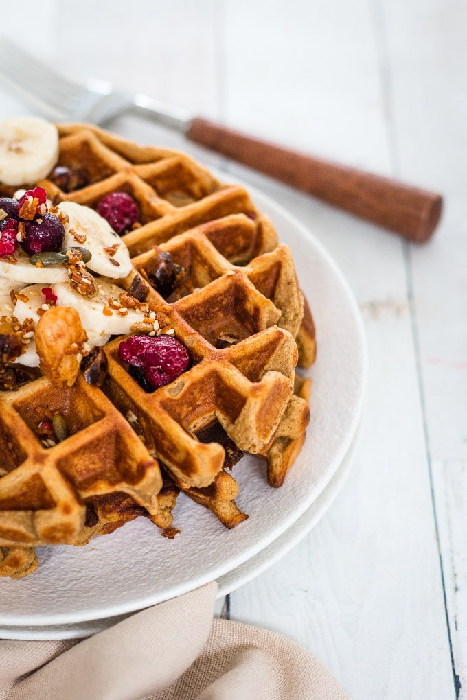 close up shot of banana waffles on a white plate topped with banana slices and berries