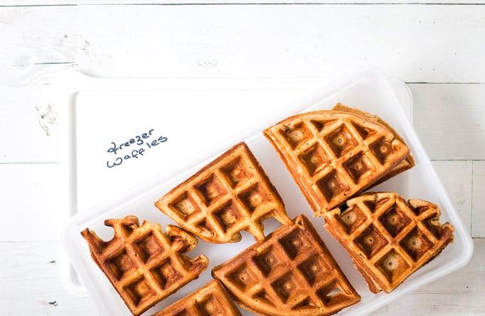 frozen waffles being transferred to a ziplock bag on which 'freezer waffles is written'