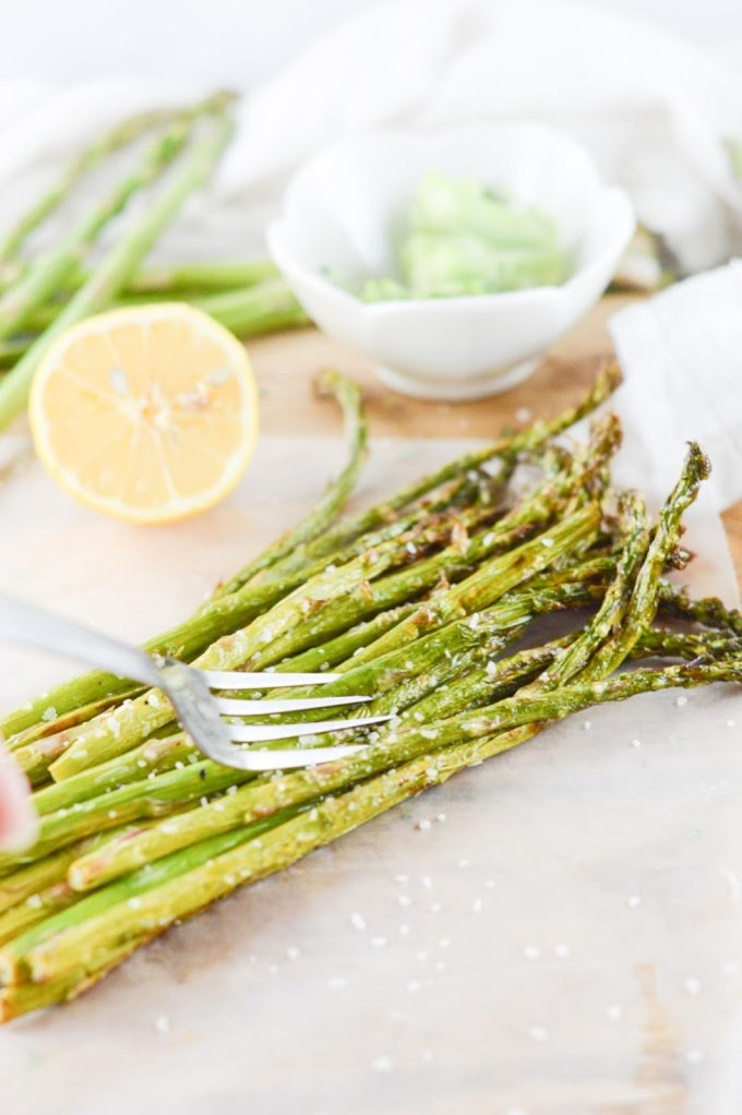 Air fryer asparagus on a wooden board with lemons in the backgroun
