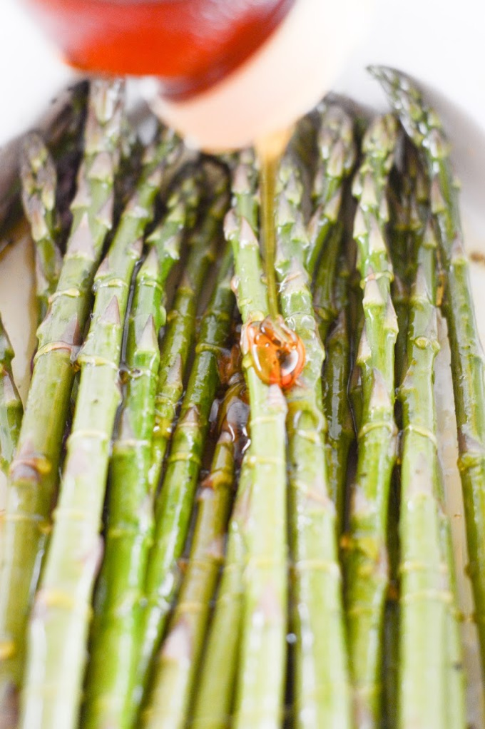 Honey being squeezed on top of asparagus